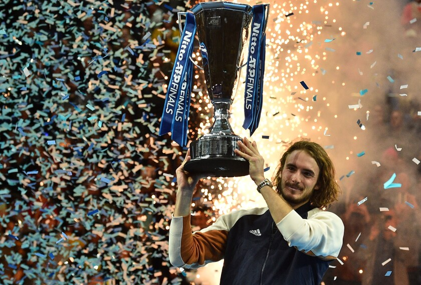 Stefanos Tsitsipas of Greece hoists the champion's trophy after winning the ATP Finals title on Nov. 17, 2019, in London.