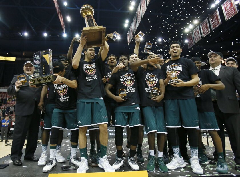 FILE - In this March 8, 2016, file photo, Green Bay's Jordan Fouse holds up the Horizon League trophy while celebrating with teammates following a 78-69 win over Wright State in an NCAA college basketball game for the conference tournament title in Detroit. The men's basketball team is in the NCAA