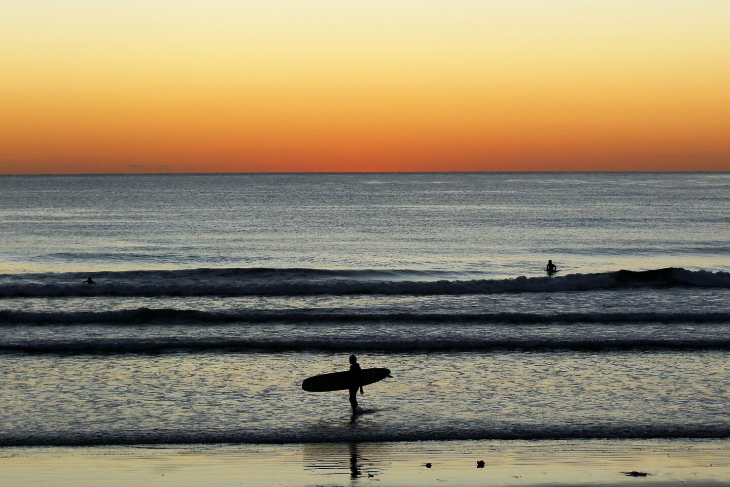 A surfer gets out of the water at Tourmaline Surfing Park in La Jolla in January.