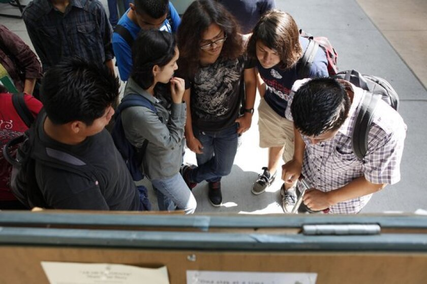 Students check class schedules on boards at East Los Angeles College in June of last year. Candidates are running for three of the Los Angeles Community College District's seven seats.