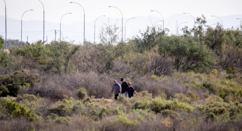 Authorities walk near the site of where a helicopter crashed after colliding mid-air with a small plane killing two people, Friday, Oct. 1, 2021, in Chandler, Ariz. The flight instructor and a student who were aboard the plane were not hurt. (Mark Henle/The Arizona Republic via AP)