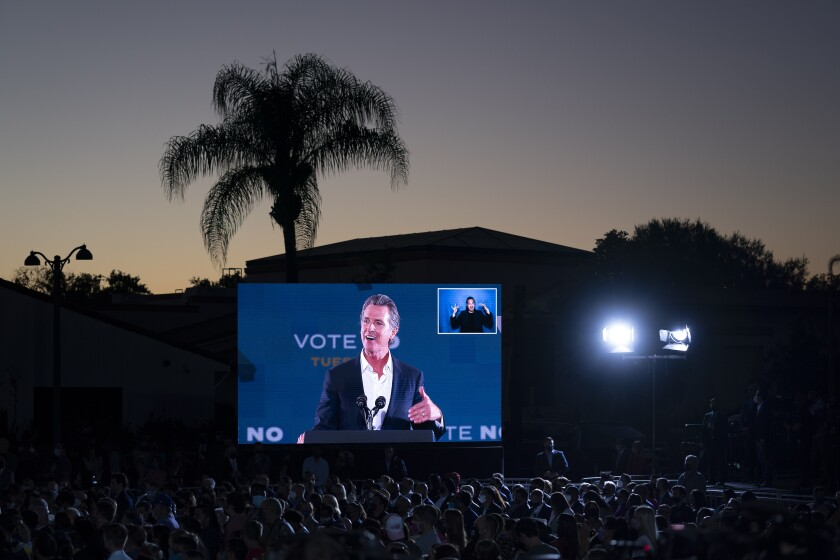 Gov. Gavin Newsom on big screen at a rally.