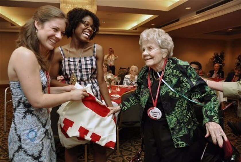 Cornell University Class of 1931 alumni, Rosemary Hunt Todd, 101-years-old, presents a spirit banner to the Class of 2006 Reunion Chairpersons from left, Krystyn Tendy and Marie-Jouvelle Auboury during Toddy's 80th Reunion at Cornell University in Ithaca, N.Y., Thursday, June 9, 2011. (AP Photo/Heather Ainsworth)