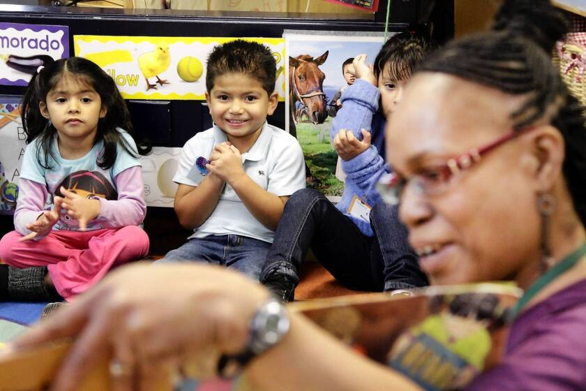 Teacher Janet Matthews gets the attention of preschoolers Daniela Caudillo, left, Henry Saenz and Esther Morataya in a PACE early education program.