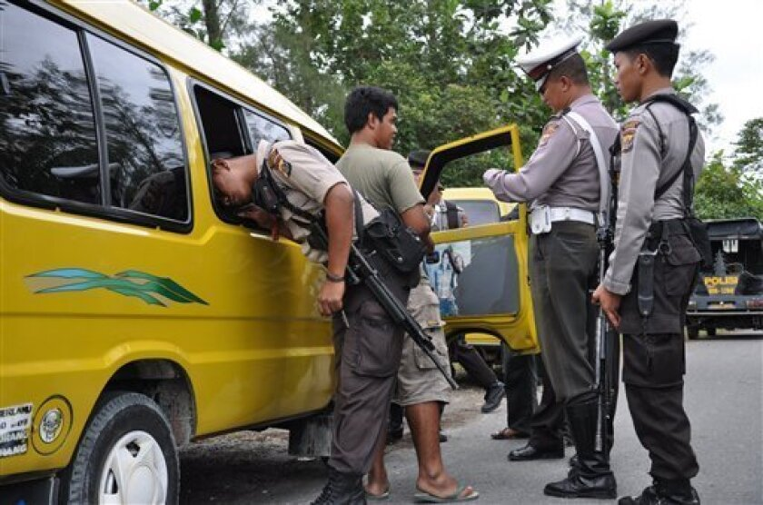 Indonesian police officers search a car at a security check point one day after an Australian employee of U.S. mining giant Freeport was shot to death by unknown assailants in Timika, Papua province, Indonesia, Sunday, July 12, 2009. A 40-member team of police and forensics specialists arrived Sunday to investigate the deadly shooting in restive Papua province, officials said. (AP Photo)
