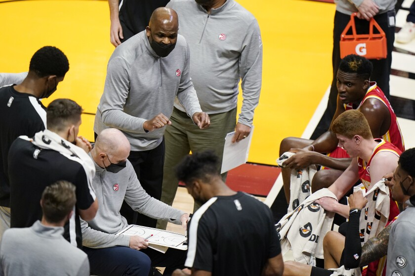 Atlanta Hawks interim coach Nate McMillan, center, gestures as he talks to players during a timeout in the first half of the team's NBA basketball game against the Miami Heat, Tuesday, March 2, 2021, in Miami. His opportunity to return to a head coach position comes with mixed feelings following Monday's firing of his friend, Lloyd Pierce. (AP Photo/Wilfredo Lee)