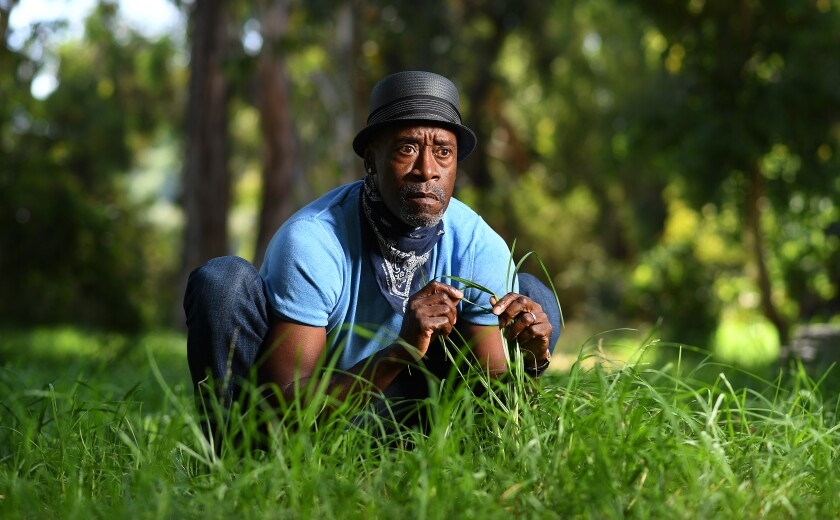 A Black man in a hat crouches down in grass
