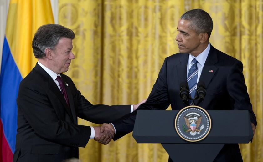 El presidente Barack Obama, derecha, se saluda con el presidente colombiano Juan Manuel Santos,desoués de reunirse en la Casa Blanca en Washington. Obama anunció el jueves que solicitará al Congreso elevar a 450 millones de dólares la cooperación a Colombia para apoyar el proceso de paz que la nación sudamericana persigue con las FARC. (AP Photo/Carolyn Kaster)
