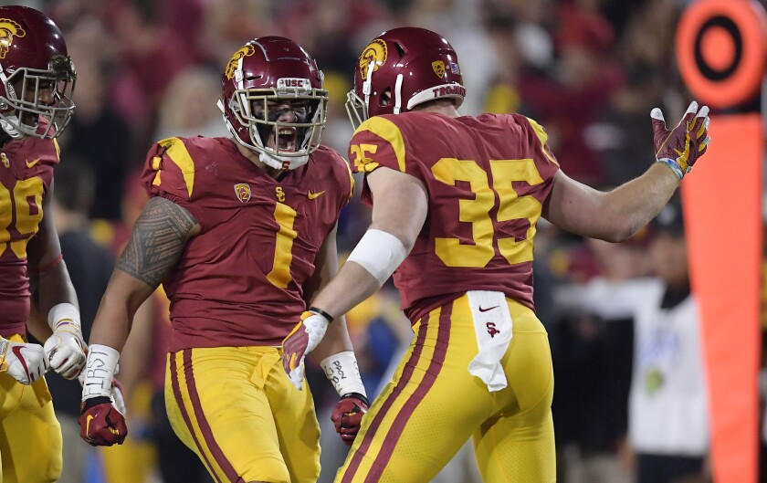 USC linebacker Palaie Gaoteote IV celebrates a sack with defensive lineman Christian Rector and linebacker Cameron Smith.