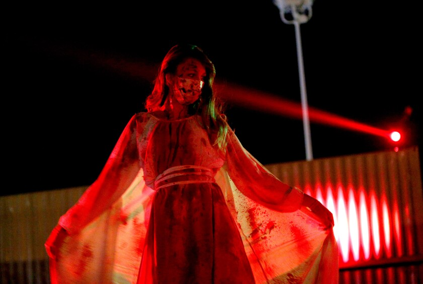 A bloody actor strikes a pose as cars pass by during a 45-minute, drive-through Urban Legends Haunt at the O.C. fairgrounds.