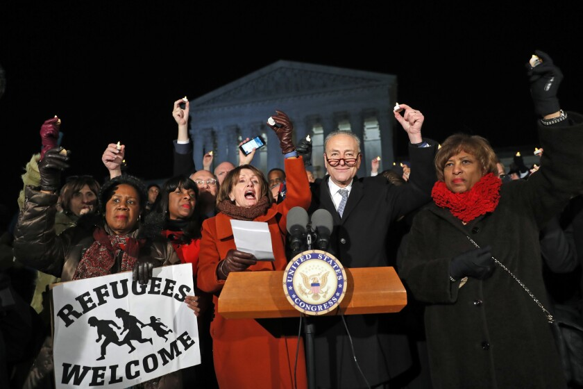Rep. Sheila Jackson Lee D-Texas, left, House Minority Leader Nancy Pelosi of Calif., Senate Minority Leader Chuck Schumer of New York, Rep. Brenda Lawrence, D-Mich., right, and other members of Congress, hold small candles aloft in front of the Supreme Court during a news conference about President Donald Trump's recent executive orders Jan. 30, 2017 in Washington, D.C.