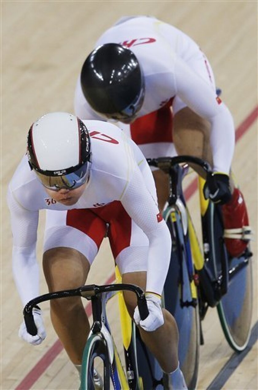 China's Gong Jinjie, left, and Guo Shang pedal on their way to set anew world record during a track cycling women's team sprint heat, at the velodrome during the 2012 Summer Olympics, Thursday, Aug. 2, 2012, in London. Gong Jinjie and Guo Shuang of China set a world record during the qualifying of the team's sprint, just seconds after the British woman also improved the mark. (AP Photo/Christophe Ena)