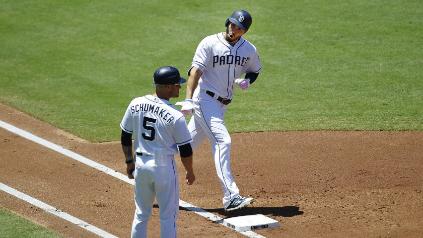 Eric Hosmer celebrates a home run with Padres first base coach Skip Schumaker, who will now hold title of associate manager.