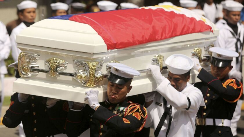 Philippine marines carry a flag-draped casket of a comrade slain in the fighting between Islamist mi
