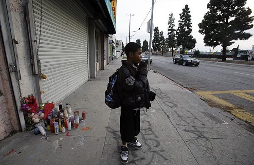 Keionta Hayes, 12, stands before a memorial of candles in the 10500 block of South Vermont Avenue, where his friend was shot earlier this month. The area is one of the deadliest in Los Angeles County.