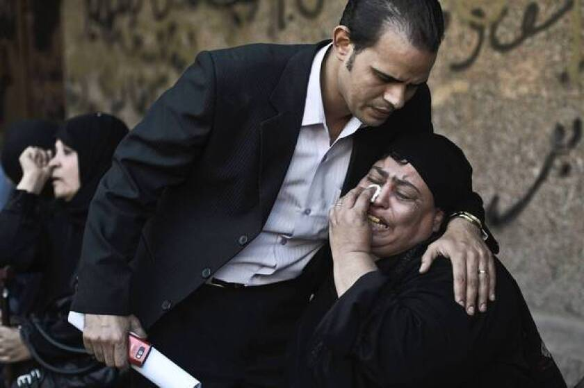 A relative of one of the victims of a shooting at a Coptic Christian Church in Cairo is comforted as she mourns at a morgue.