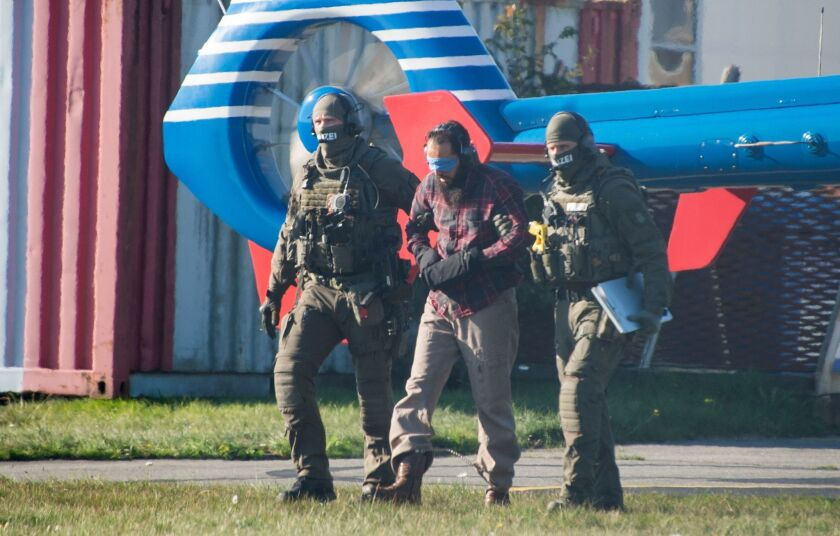 Police officers escort Moroccan terror accomplice Mounir el Motassadeq (C) after he was brought with a helicopter from the Fuhlsbuettel prison to the airport in Hamburg, northwestern Germany, on Monday.