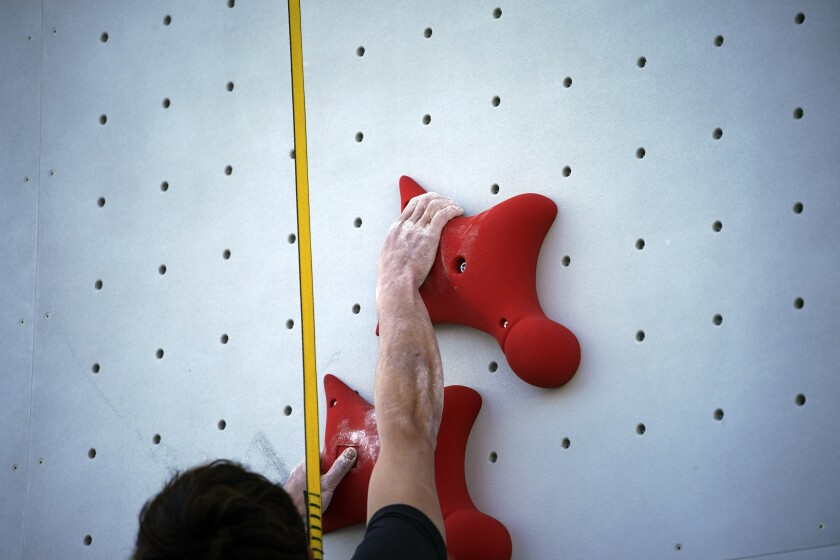 A Tokyo 2020 Olympic Games Organizing staff climbs the wall in the test event of Speed Climbing in preparation for the Tokyo 2020 Olympic Games at Aomi Urban Sports Park Friday, March 6, 2020, in Tokyo. The recent outbreak of the coronavirus has forced them to cancel or postpone several. But they allowed a sport climbing event on Friday to go ahead, with a few restrictions: like the absence of elite athletes. (AP Photo/Eugene Hoshiko)