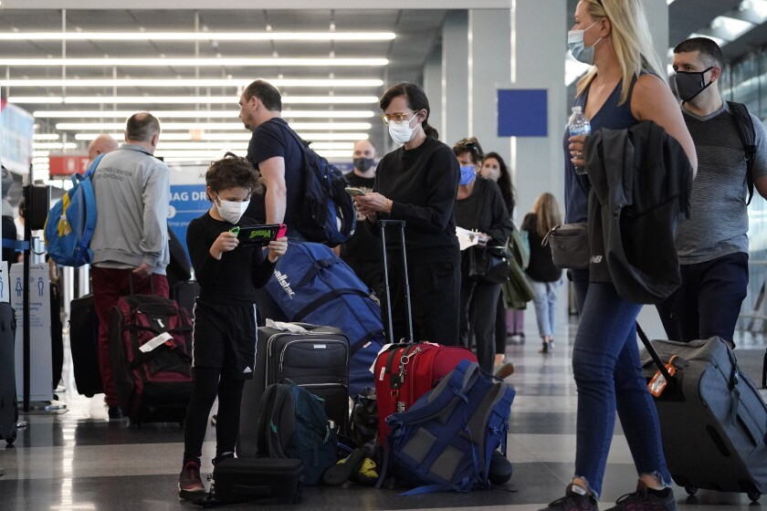 Travelers are lining up at O'Hare airport in Chicago, Friday, July 2, 2021