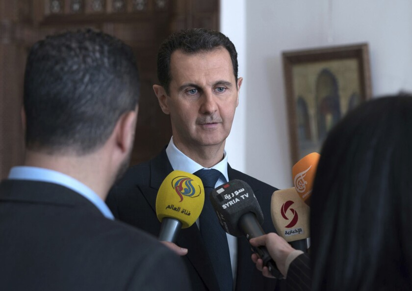 FILE - In this March 4, 2018 file photo, provided by the official Facebook page of the Syrian Presidency, Syrian President Bashar Assad speaks with reporters in Damascus, Syria. Assad issued a decree Sunday, May 2, 2021, granting amnesty and reducing sentences for several categories of crime committed before May 2, state news agency SANA said. The amnesty came days before Muslims celebrate Eid el-Fitr, the feast that marks the end of the Muslim holy month of Ramadan and ahead of the May 26 presidential elections. (Syrian Presidency Facebook Page via AP, File)