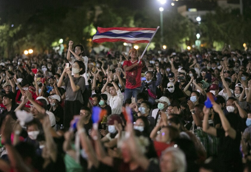 A Thai demonstrator waves the national flag amid a pro-democracy crowd in Bangkok.