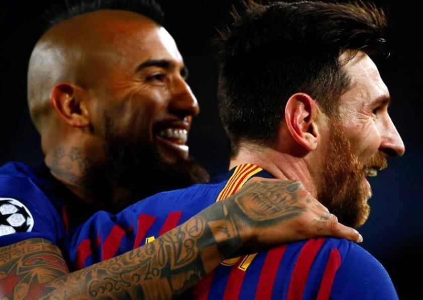 El delantero argentino del FC Barcelona Leo Messi (d) celebra con el chileno Arturo Vidal su segundo gol, y tercero del equipo ante el Olympique de Lyon, durante el partido de vuelta de los octavos de final de la Liga de Campeones que FC Barcelona y Olympique de Lyon jugaron anoche en el Camp Nou, en Barcelona. EFE