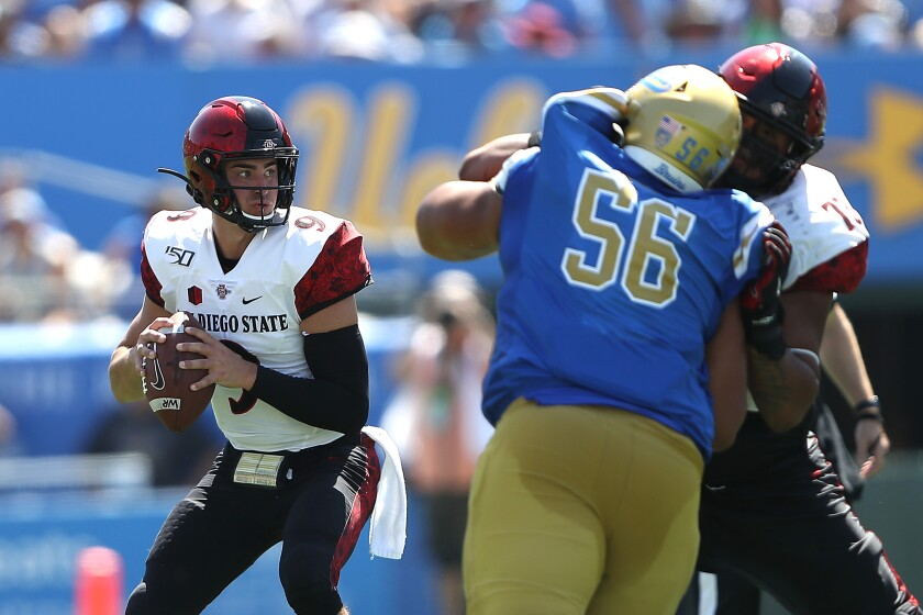San Diego State quarterback Ryan Agnew looks to pass as UCLA's Atonio Mafi rushes during the first half of Saturday's game at the Rose Bowl.