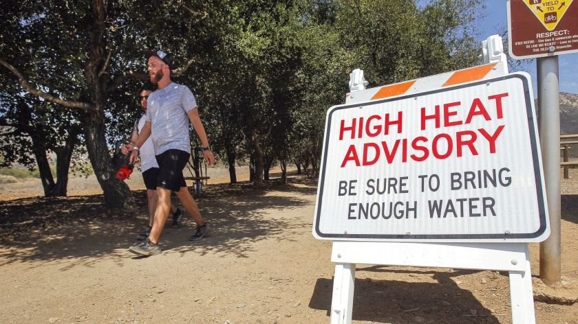 Chris Capeau, right, and Ryan Williams walk toward the parking lot after hiking the Iron Mountain Trail in Poway on Thursday. Iron Mountain and other popular trails will be closed to the public the next few days because of predicted extreme heat.