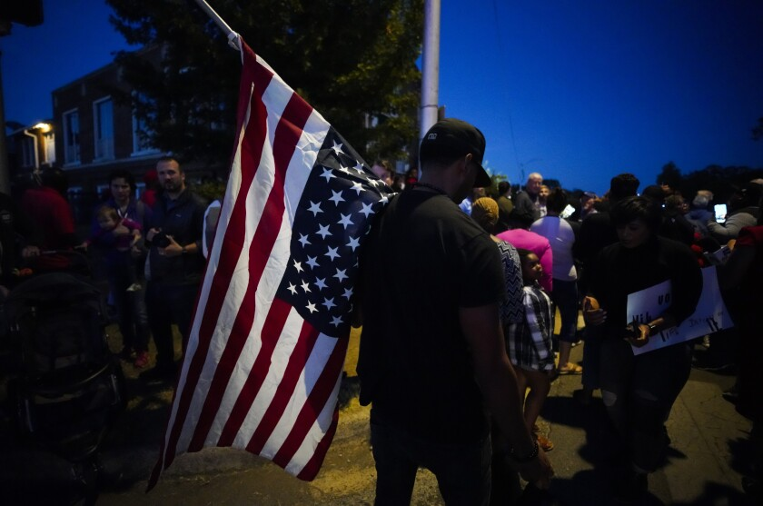 """A large crowd of protesters, including a man carrying an upside-down American flag, gather outside the house where Atatiana Jefferson was shot Saturday and killed by police, during a community vigil for Jefferson on Sunday, Oct. 13, 2019, in Fort Worth, Texas. A white police officer who killed the black woman inside her Texas home while responding to a neighbor's call about an open front door """"didn't have time to perceive a threat"""" before he opened fire, an attorney for Jefferson's family said. (Smiley N. Pool/The Dallas Morning News via AP)"""