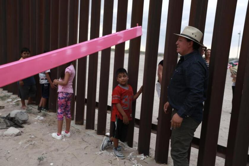 Fotografía fechada el 28 de julio de 2019, que muestra al arquitecto Ronald Rael (d), mientras participa en la colocación de sus balancines, en la frontera de Ciudad Juárez (México), con Estados Unidos. EFE/ Luis Torres
