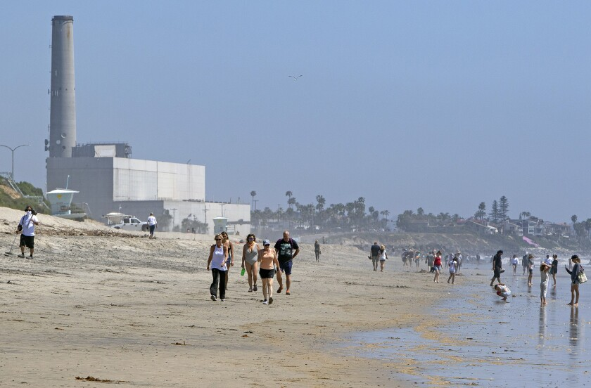 People stroll along the shore of Carlsbad State Beach after it re-opened Monday.
