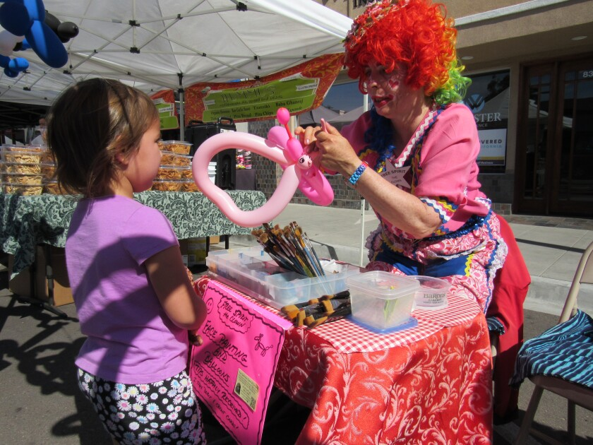 A clown gets creative with a balloon for a child at a recent Farmers Market event in downtown La Mesa. The city is planning on starting a special fund to help bring more events to the Village area.
