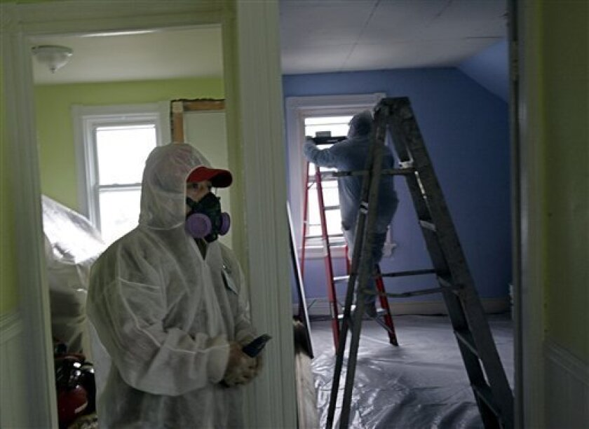 In this Thursday, Feb. 23, 2006 photo, contractors Luis Benitez, foreground, and Jose Diaz, background, clean up lead paint in a contaminated building in Providence, R.I. A federal panel recommended Wednesday, Jan. 4, 2012 that the threshold for lead poisoning in children should be lowered. If adopted by government officials, hundreds of thousands of additional U.S. children could be classified as having lead poisoning. Recent research persuaded panel members that children could suffer harm from concentrations of lead lower than the old standard, Centers for Disease Control and Prevention officials said. (AP Photo/Chitose Suzuki)