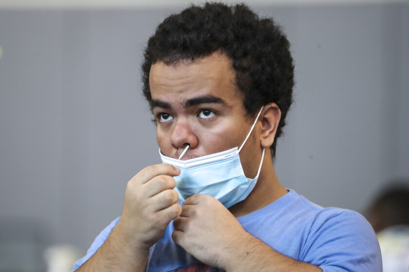 Jorge Morales, 18, swabs his nose to test for the coronavirus