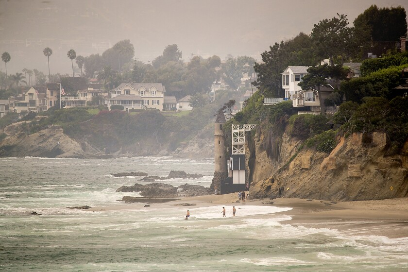 Beachgoers enter the water in front of a tower at Victoria Beach in Laguna Beach.