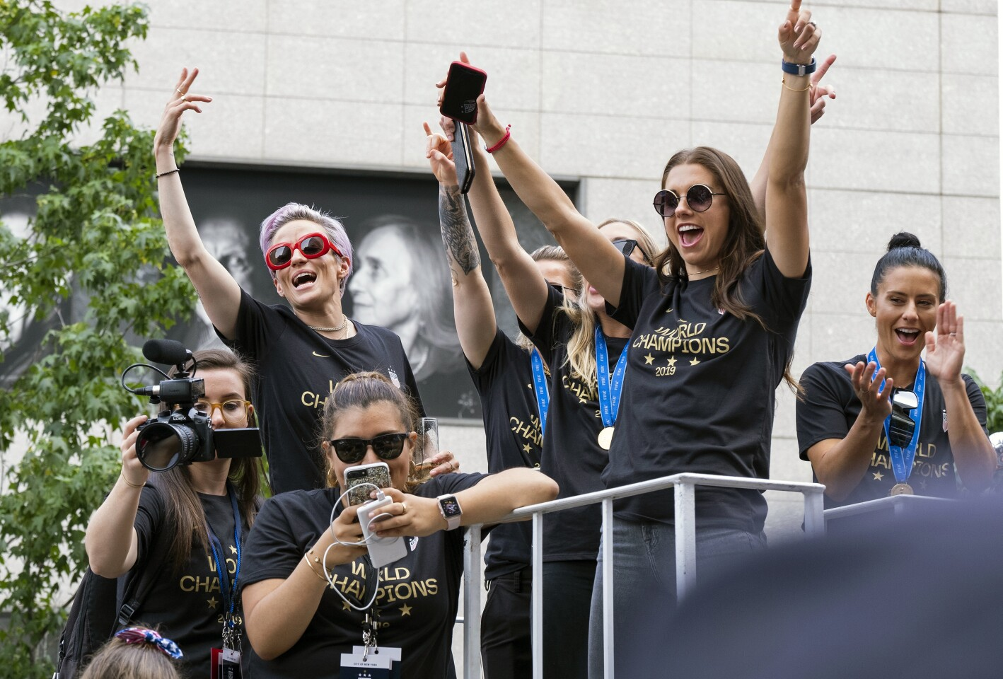 Member of the U.S. women's soccer team, including Megan Rapinoe, rear left, and Alex Morgan, right foreground, stand on a float before being honored with a ticker tape parade along the Canyon of Heroes in New York.