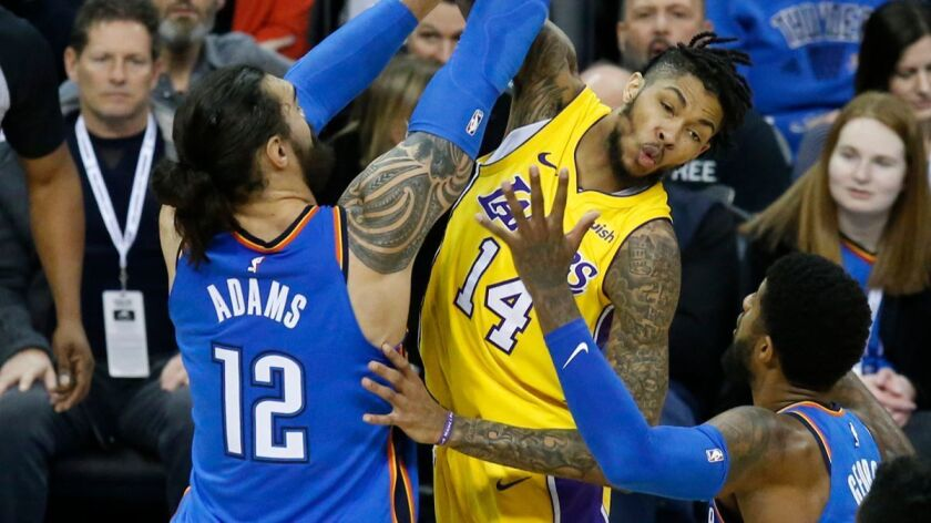 Lakers forward Brandon Ingram (14) passes between Oklahoma City Thunder center Steven Adams (12) and forward Paul George in the first half on Wednesday, Jan. 17, 2018.
