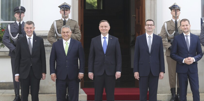 Poland's President Andrzej Duda, center, and Prime Minister Mateusz Morawiecki, second right, are taking a family photo with Slovak Prime Minister Igor Matovic, right, Czech Prime Minister Andrej Babis, left and Hungarian Prime Minister Viktor Orban, second left, at the start of a Visegrad Group summit in Warsaw, Poland, Friday, July 3, 2020, as Poland takes the rotating presidency of the regional cooperation group.(AP Photo/Czarek Sokolowski)