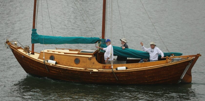 """Keith """"Moley"""" Wilson, Brooks """"Badger"""" Iler and Bob """"Ratty"""" Germann sail the Ragmeg, a rare 27-foot wooden dory, out of the Oceanside Harbor to the San Diego Wooden Boat Show in San Diego Friday morning."""