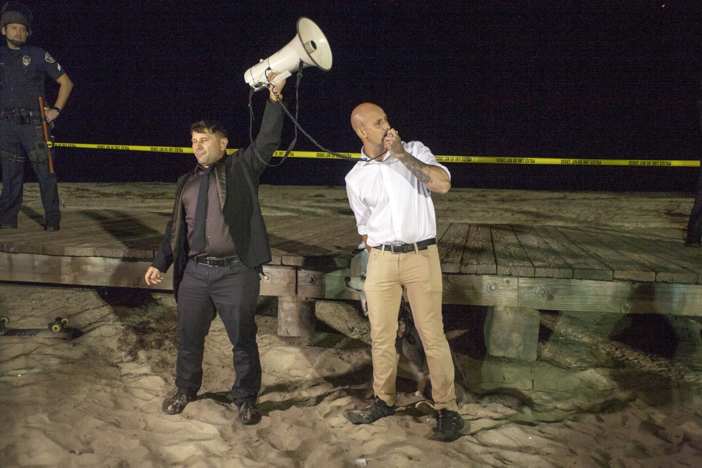 As group member Bassad Pesci holds the bullhorn, Onward America organizer Johnny Benitez thanks police for their presence and restraint during the group's rally Sunday night at Main Beach in Laguna Beach.