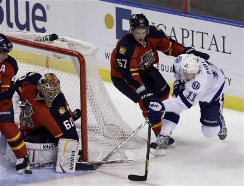 Florida Panthers goalie Jose Theodore (60) blocks a shot by Tampa Bay Lightning's Tom Pyatt (11) in the first period of an NHL hockey game as Marcel Goc (57) defends in Sunrise, Fla., Saturday, Feb. 16, 2013. (AP Photo/Alan Diaz)