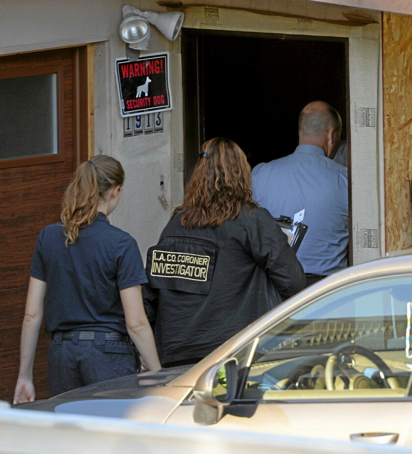 In this Wed., July 22, 2015 photo, police and coroner investigators enter the home where a homicide took place on Nelson Avenue in Redondo Beach, Calif. A California man has been charged in the stabbing death of his girlfriend, whose life as a lawyer was depicted on a short-lived reality television show. Fifty-one-year-old Robert Reagan of Redondo Beach was charged with murder Friday, July 24, 2015, in the death of 47-year-old Loredana Nesci. (Scott Varley/Daily Breeze via AP)