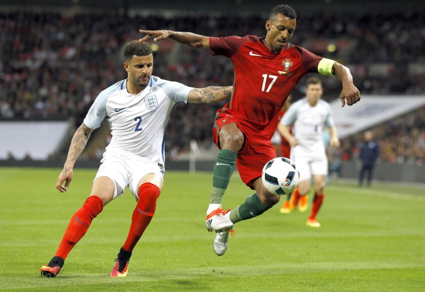 England's Kyle Walker, left, vies for the ball with Portugal's Nani during the international friendly soccer match between England and Portugal at Wembley stadium in London, Thursday, June 2, 2016. (AP Photo/Kirsty Wigglesworth)