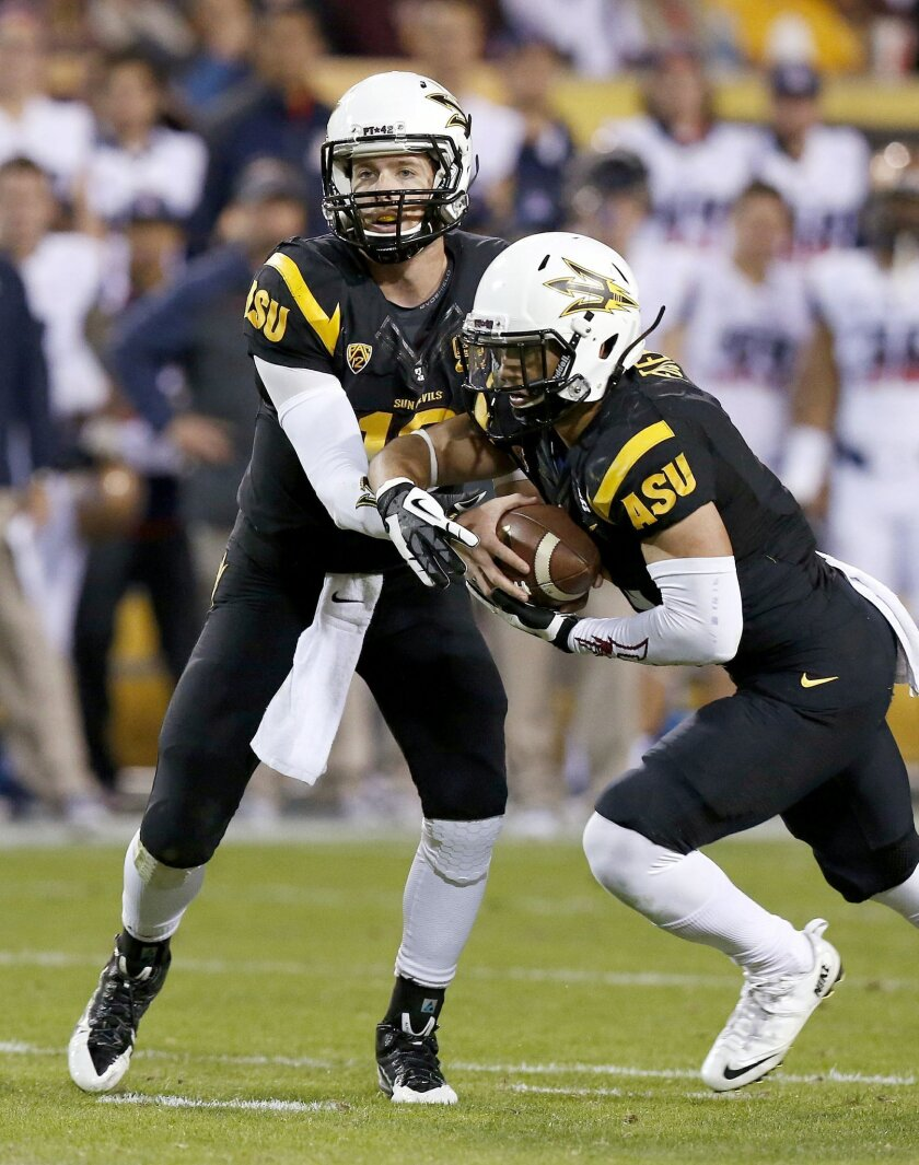 Arizona State's D.J. Foster, right, gets the ball from Taylor Kelly during the first half of an NCAA college football game against Arizona, Saturday, Nov. 30, 2013, in Tempe, Ariz. (AP Photo/Ross D. Franklin)