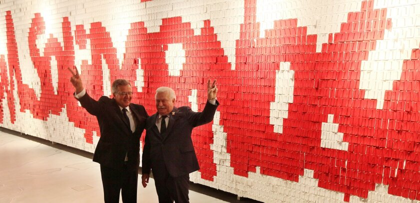 Poland's President Bronislaw Komorowski, left, and former president and first Solidarity leader Lech Walesa flash victory sign in front of a wall with the Solidarity logo composed of red and white note papers at the new European Solidarity Center that opened in Gdansk, Poland, Sunday, Aug. 31, 2014. The center shows the history of Eastern Europe's first free trade union that in 1989 toppled Poland's communist rulers and paved the way for similar change in other countries of the Soviet Bloc .(AP Photo/Czarek Sokolowski)
