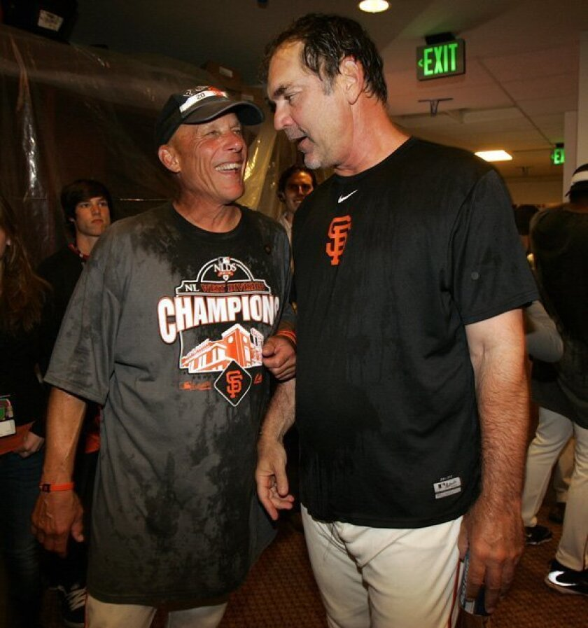San Francisco Giants manager Bruce Bochy, left, shakes hands with fans after an NL West-title-clinching win Oct. 3, 2010.