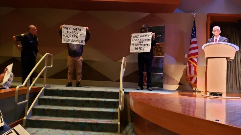 Two masked protestors and Library Foundation president Ken Brecher at ALOUD on Sept. 17, 2018. Photo