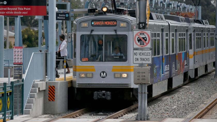 A train heading toward Santa Monica pulls into the Farmdale Avenue station in the middle of the Metro Expo Line.
