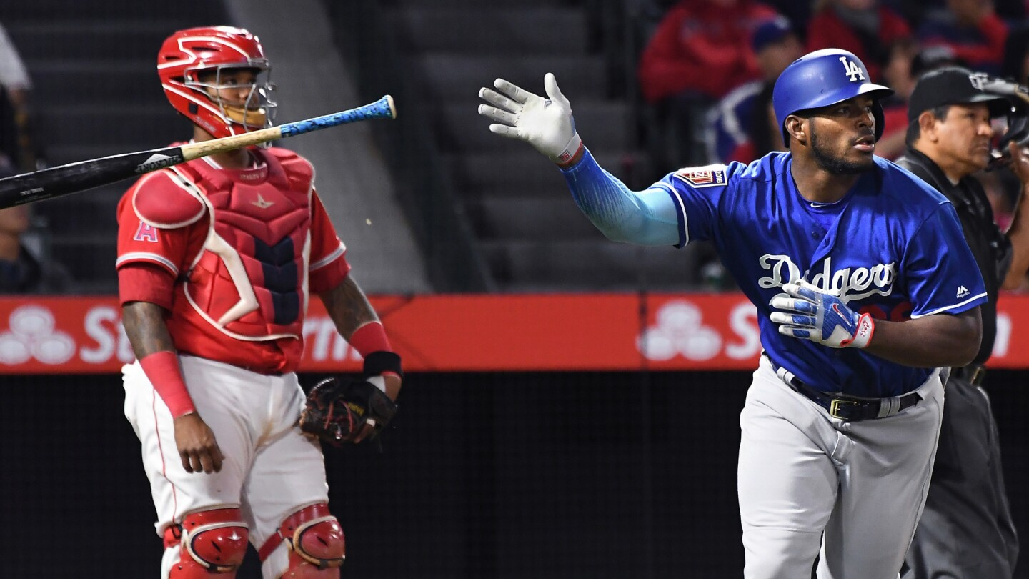 Dodgers outfielder Yasiel Puig hits a solo home run against the Angels in the seventh inning on March 25.