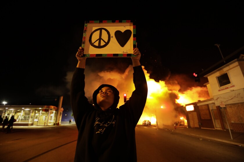 """A woman holds a """"peace and love"""" sign during the George Floyd protests in Minneapolis on May 29."""